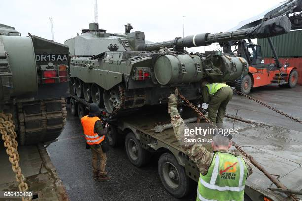 A crew secures a British Army Challenger 2 tank of the 5th Battalion The Rifles to a truck trailer after the tank and other heavy vehicles arrived by...