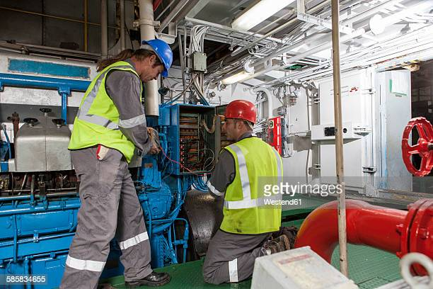 Crew working in engine room on a ship