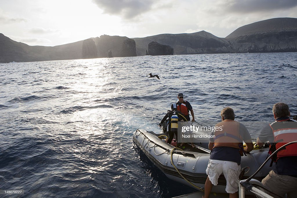 Crewman help scuba divers on an inflatable boat : Stock Photo