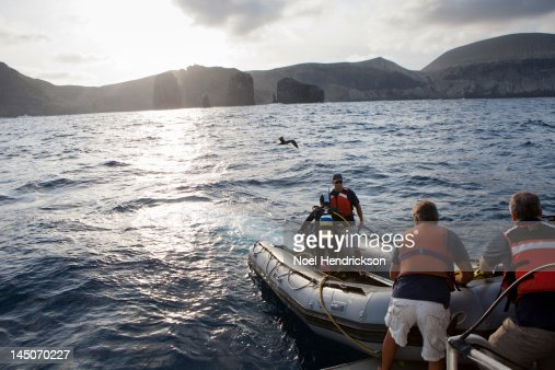 Crewman help scuba divers on an inflatable boat : Foto stock