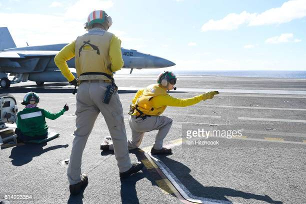Crewman launch a US Navy Super Hornet off the deck of the USS Ronald Reagan on July 14 2017 in Townsville Australia USS Ronald Reagan is a 1092 foot...