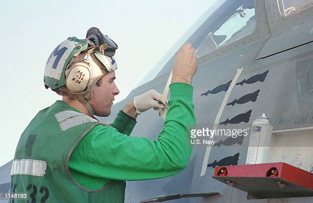 A crewman of the USS Enterprise takes advantage of a lull in activities in between air strikes against Iraq to paint icons of bombs on a squadron...