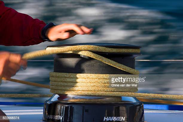 Crewmember Trimming Sails on Winch