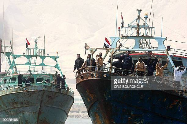 Crewmembers of the Egyptian fishing ships Ahmad Samara and Momtaz I wave as they arrive at the port in Ataka 170 kms northeast of Cairo on August 23...