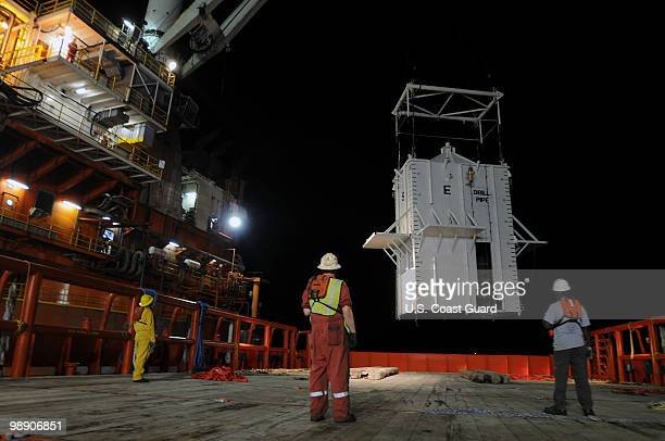Crewmen aboard the motor vessel Joe Griffin look on as the mobile offshore drilling unit Q4000 lowers a pollution containment chamber May 6 2010 in...