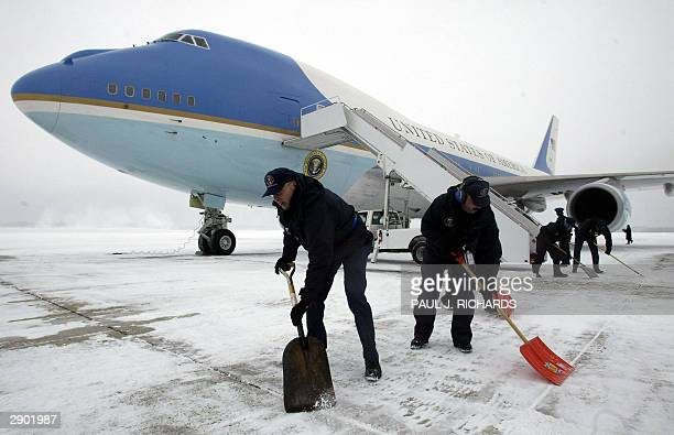 Crewmen at Andrews AFB shovel snow prior to the arrival of US President George W Bush and prepare Air Force One for flight 26 January 2004 to Little...