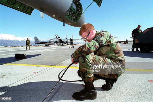 Crewmen Earl J Adams checks the pressure of nitrogen being supplied to the front landing gear tire as the F15E Strike Eagles prepare for a sortie in...