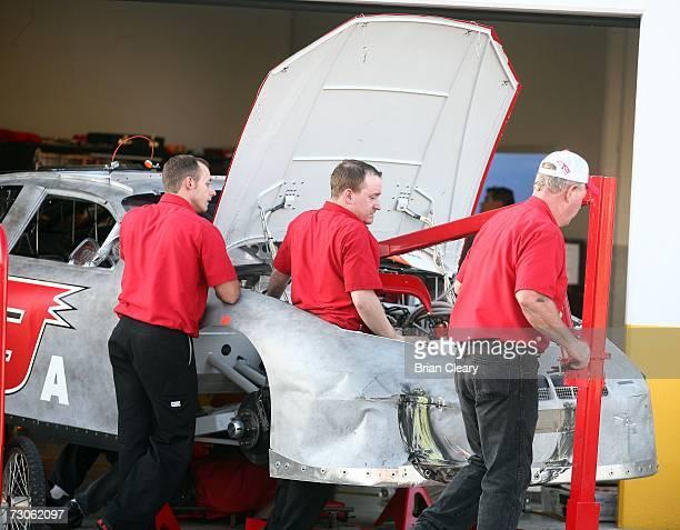 Crewmen work on Bill Elliott's damaged race car in the garage area during Busch series winter testing at Daytona International Speedway January 21...