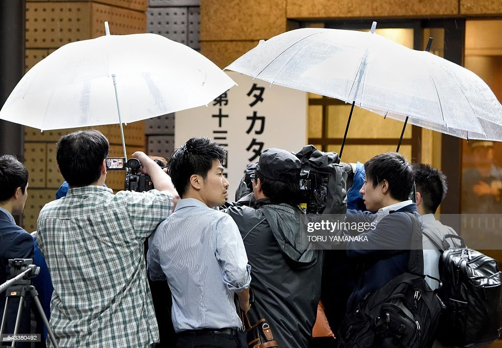 TV crews and jounalists gather to interview a shareholder of crisis-hit airbag supplier Takata before a shareholders meeting in Tokyo on June 28, 2016. The Japanese car parts maker Takata held the 13th ordinary shareholders meeting following the global recall of several automakers caused by defect of the company's airbags. / AFP / TORU