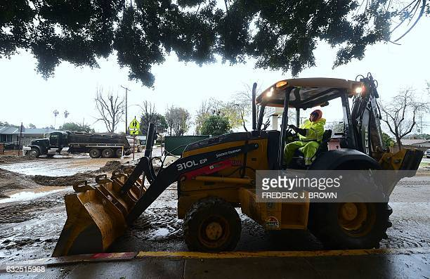 Crews clear mud from the roads in Duarte California January 23 2017 as another night of rain brought more thick mud and debris flowing past homes /...