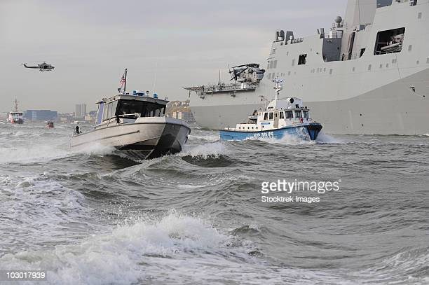 Crews from the coast guard and police departments escort USS New York as it sails into New York Harbor.