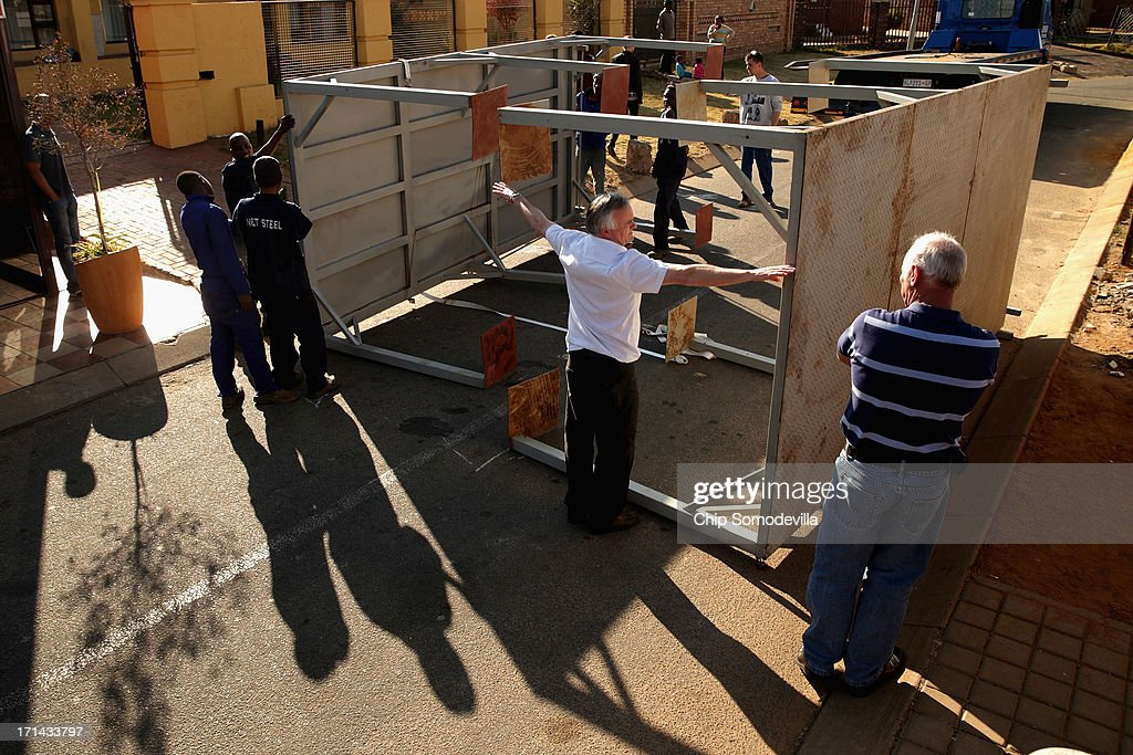 Crews measure steel platforms while building a television stage for CBS News across the street from former President Nelson Mandela's Soweto home, which now serves as a museum, June 24, 2013 in Johannesburg, South Africa. News media companies have rented space along Vilikazi Street to broadcast from in the event of Mandela's death. South African President Jacob Zuma confirmed that Mandela's condition has become critical since he was admitted to the hospital over two weeks ago for a recurring lung infection.