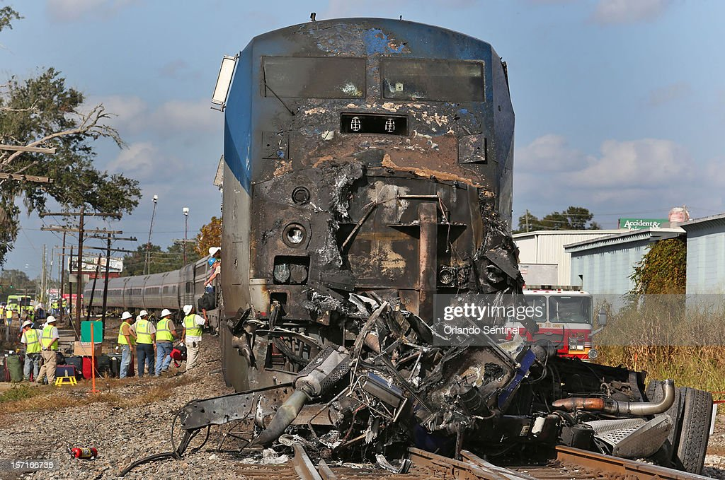 Crews unload luggage, in background, Thursday, November 29, 2012, after a Miami-bound Amtrak passenger train struck and killed a truck driver at the intersection of Orange Avenue and Nela Avenue in Orlando, Florida.