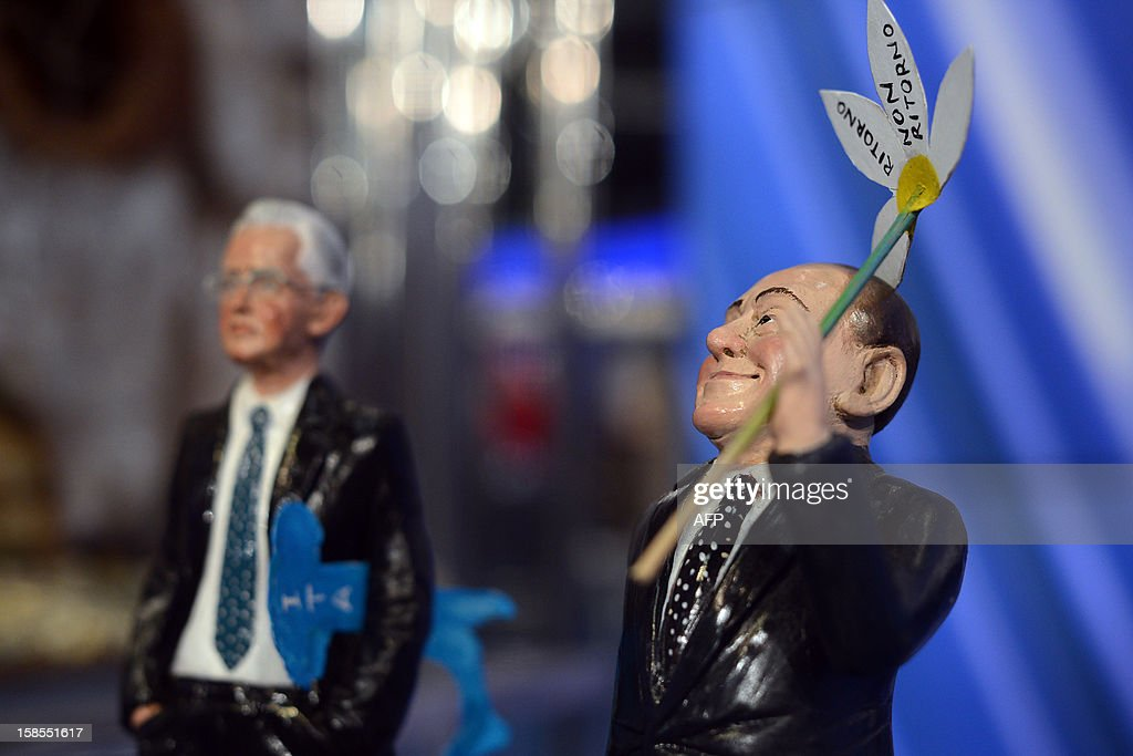 Crib figurines showing former Italian Prime Minister Silvio Berlusconi (R) and current Prime Minister Mario Monti are displayed on the set of RAI 1 television programme 'Porta a Porta' on December 18, 2012 in Rome. Silvio Berlusconi the day before said a German-dominated Europe had imposed austerity on Italy as the three-time prime minister prepares for his sixth election campaign in two decades in politics. Flower reads 'No come back'.