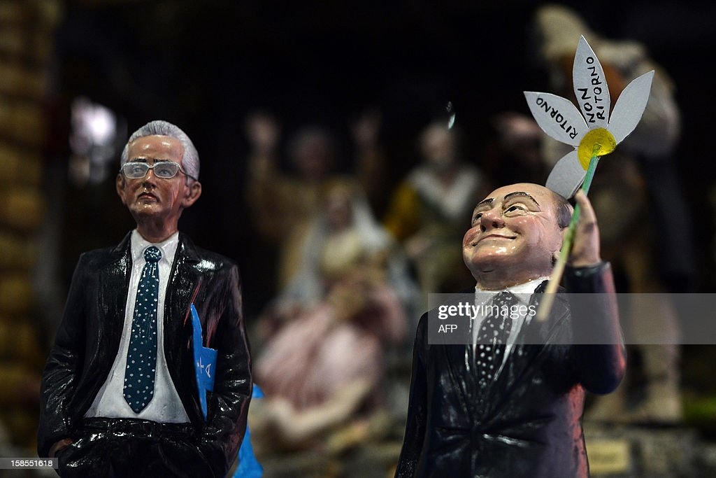 Crib figurines showing former Italian Prime Minister Silvio Berlusconi (R) and current Prime Minister Mario Monti are displayed on the set of RAI 1 television programme 'Porta a Porta' on December 18, 2012 in Rome. Silvio Berlusconi the day before said a German-dominated Europe had imposed austerity on Italy as the three-time prime minister prepares for his sixth election campaign in two decades in politics. Flower reads 'No come back'. AFP PHOTO / FILIPPO MONTEFORTE