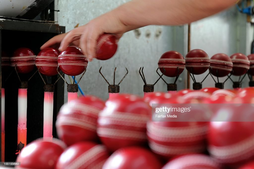 Cricket balls are removed rom the laquering machine at the Kookaburra factory at Moorabbin in Melbourne, October 24, 2012. This iconic manufacturer of Australian cricket balls is angered that Cricket Australia intends to introduce the English-made Dukes balls into domestic games. Kookaburra has virtually monopolised the local cricket ball market for the past 122 years. (Photo by Penny Stephens/Fairfax Media/Fairfax Media via Getty Images).