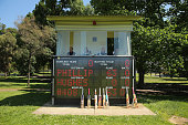 Cricket bats and caps belonging to the players are placed near the scoreboard which displays a tribute to Phillip Hughes during a match between...