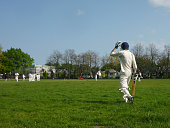 A wicket has just fallen in a cricket match, and the new Batsman heads out onto the field to face up.
