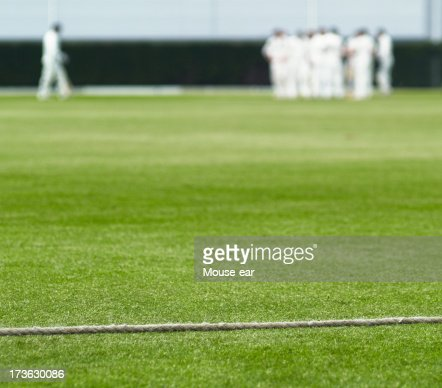 Cricket boundary rope and walking batsman