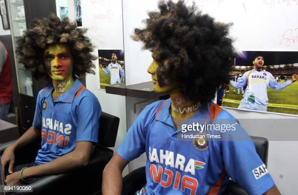A cricket fan at the Dadar National Haircraft Saloon at Dadar ensuring that he will emerge happy from the Wankhede stadium no matter which team wins...