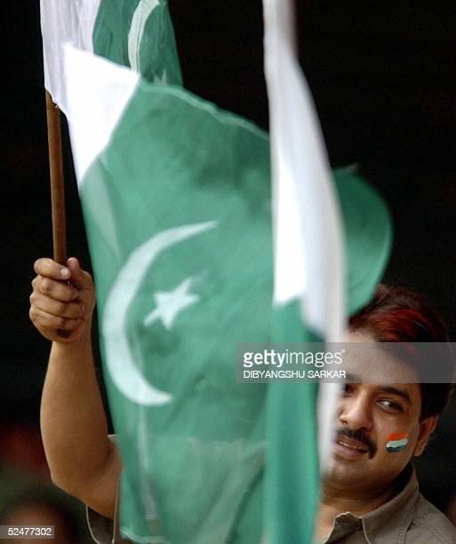 A cricket fan waves the Pakistan flag whilst wearing the Indian colours on his cheek during the second day of the third and final Test match in the...