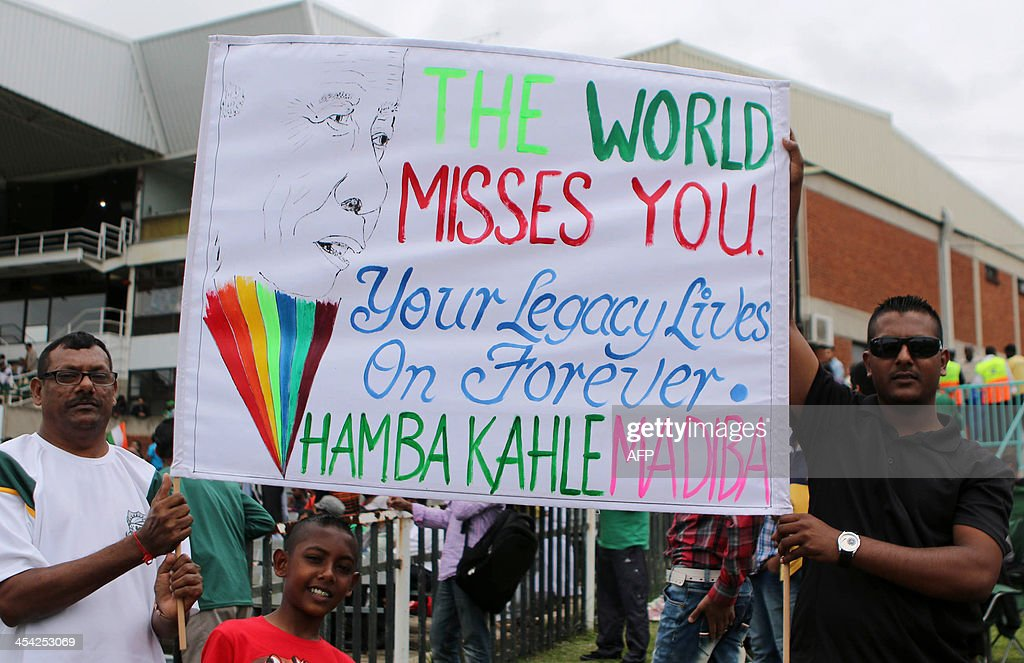Cricket fans hold a poster paying homage to the late South African President Nelson Mandela during the One day International (ODI) Cricket Match between India and South Africa at SAHARA Stadium Kingsmead in Durban on December 8, 2013.