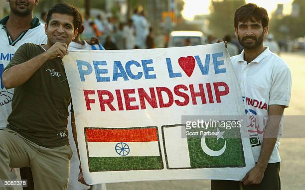 Cricket fans hold a sign which says 'Peace Love Friendship' after the first Pakistan v India one day international match played at the National...