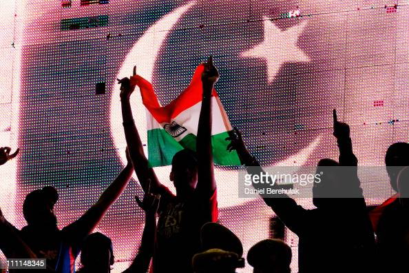 Cricket fans hold an Indian flag as the flag of Pakistan is displayed on an electronic scoreboard during the 2011 ICC World Cup second SemiFinal...