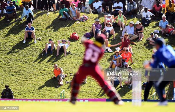 Cricket fans watch as West Indies cricketer Jason Mohammed plays a shot during the One Day International match between England and West Indies at the...