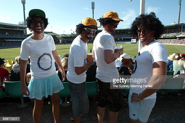 Cricket fans with faces painted dark brown and wearing afro wigs watch the play from Yabba's Hill during the Australia v South Africa onedayseries at...