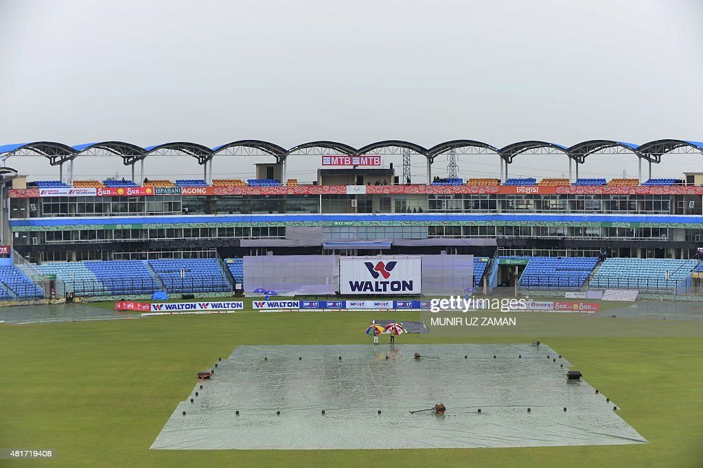 Cricket officials walk across the playing surface as the rain delayed play on the fourth day of the first cricket Test match between Bangladesh and...