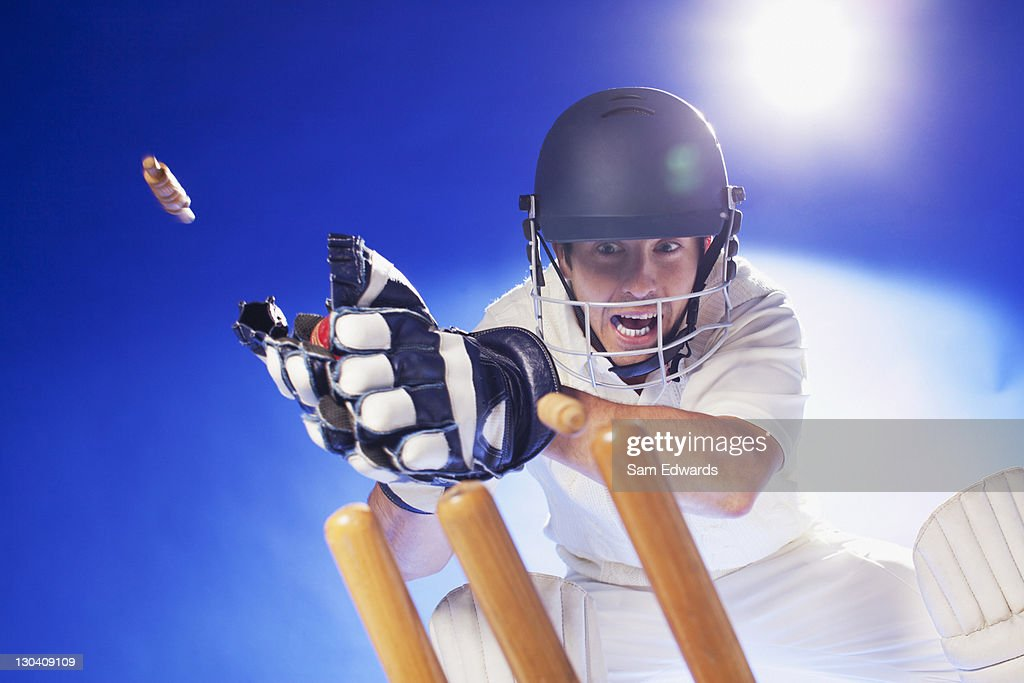 Cricket player lunging for bats : Stock Photo
