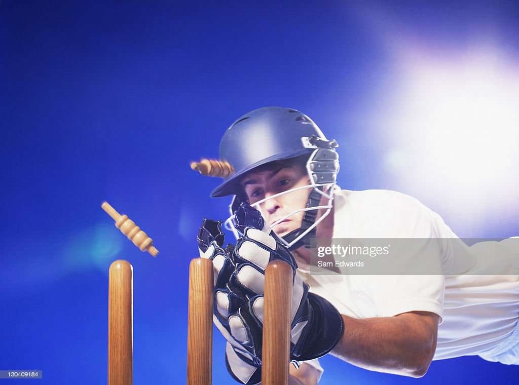 Cricket player reaching for bats : Stock Photo