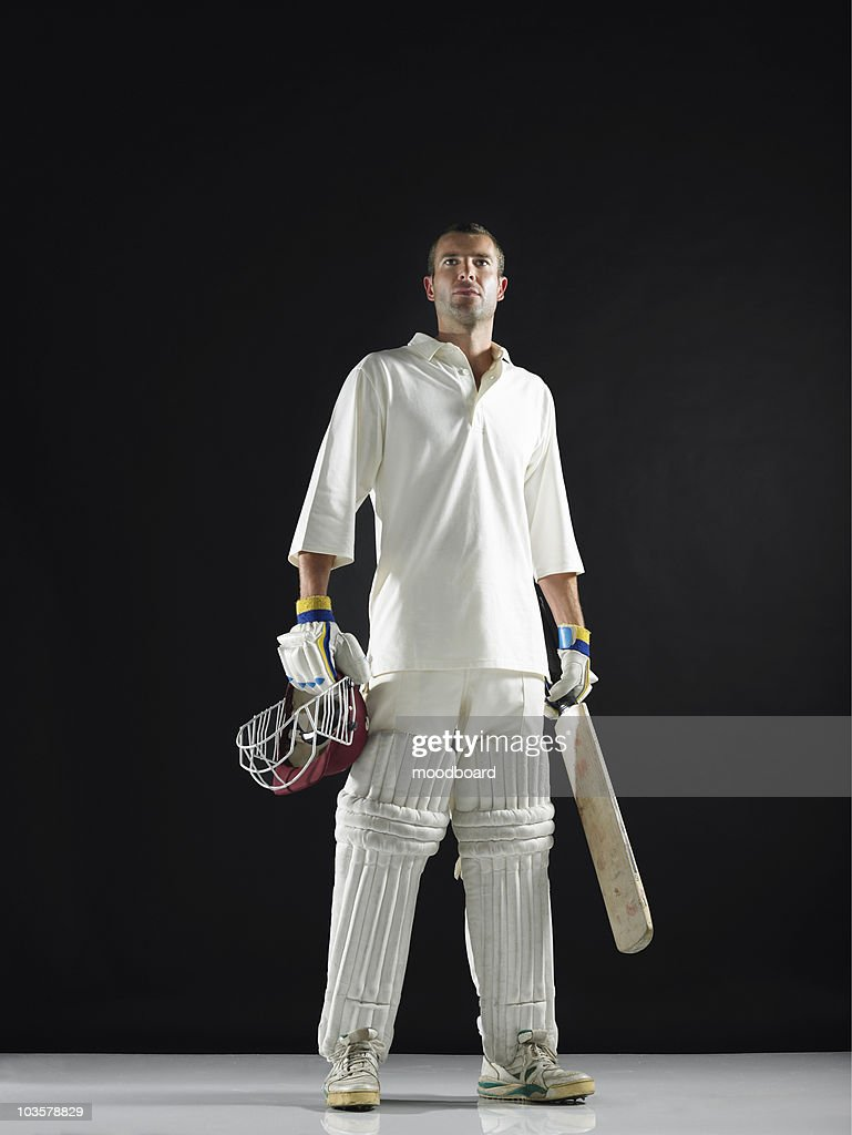 Cricket player, standing holding cricket bat, low angle view : Stock Photo
