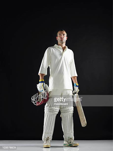 Cricket player, standing holding cricket bat, low angle view