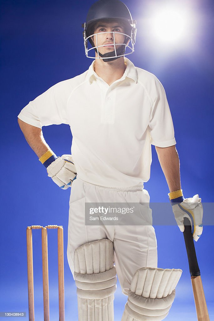 Cricket player standing with bat : Stock Photo