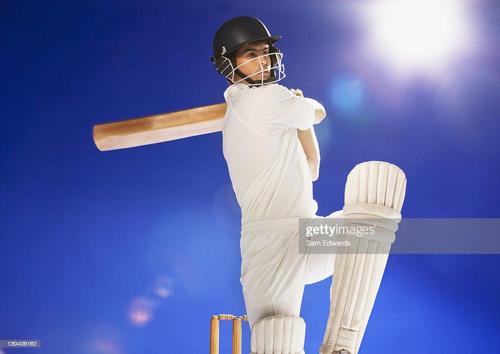Cricket player swinging bat : Stock Photo