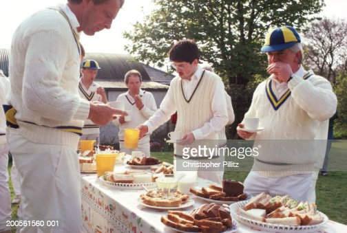 Cricket players eating and drinking during break : Stock Photo