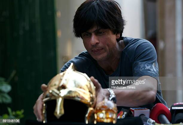 Cricket Shahrukh Khan unveiling the gold plated helmet trophy that will be given to the man of the match at his residence Mannat