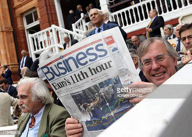 A cricket spectator reads the business section of a newspaper before the beginning of the first test match between England and India at Lord's...