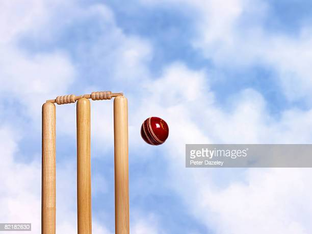 Cricket stumps and cricket ball against blue sky