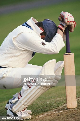 Cricketeer holding bat, crouching, side view : Stock Photo