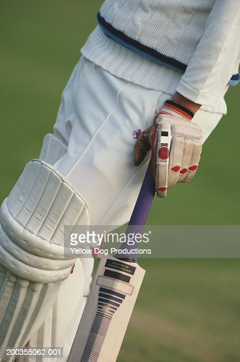 Cricketeer holding bat, low section, side view : Stock Photo
