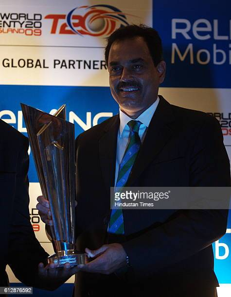 Cricketer Dilip Vengsarkar poses with the newly unveiled ICC World T20 trophy in Mumbai