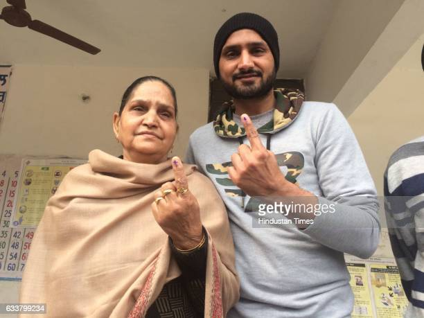 Cricketer Harbhajan Singh with his mother Avtar Kaur showing their fingers after casting their votes on February 4 2017 in Jalandhar India Punjab on...