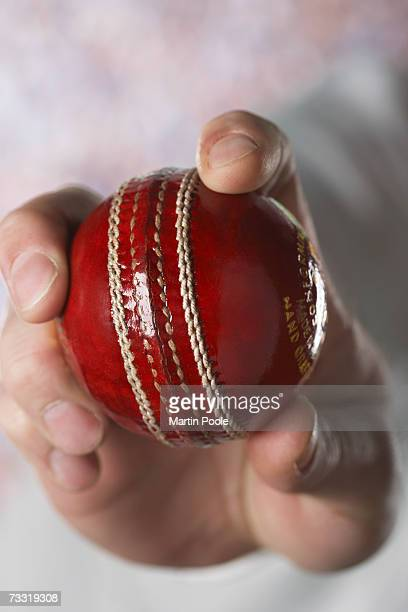 Cricketer holding cricket ball, close-up of hand and ball
