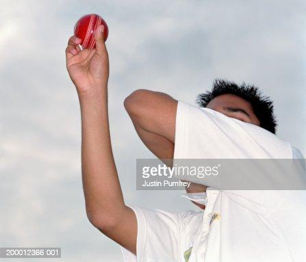 Cricketer throwing cricket ball, close-up : Stock Photo