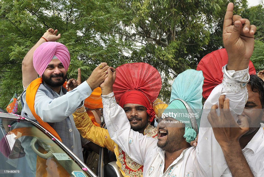 Cricketer turned politician and BJP MP from Amritsar Navjot Singh Sidhu gets warm welcome by his supporters during his visit in his constituency after a long time on September 4, 2013 in Amritsar, India. Addressing media Navjot Singh Sidhu justified his absence for nearly eight months from his constituency Amritsar. A non-governmental organisation had, earlier this month, put up posters around Amritsar declaring Sidhu a 'missing person' and even announcing a reward to anyone bringing him back.