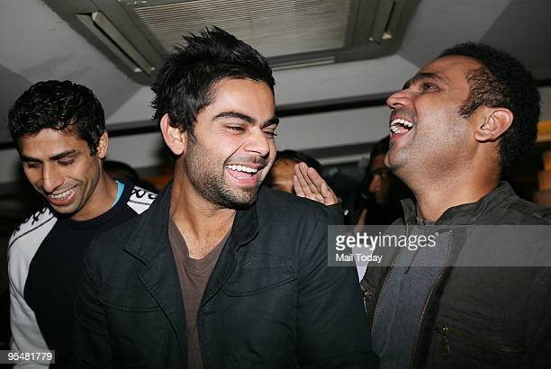 Cricketers Ashish Nehra Virat Kohli and Virender Sehwag at a party in the honour of Virender Sehwag following his stupendous Test performance against...