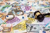 crime concept - handcuffs, gavel dollar and euro bills